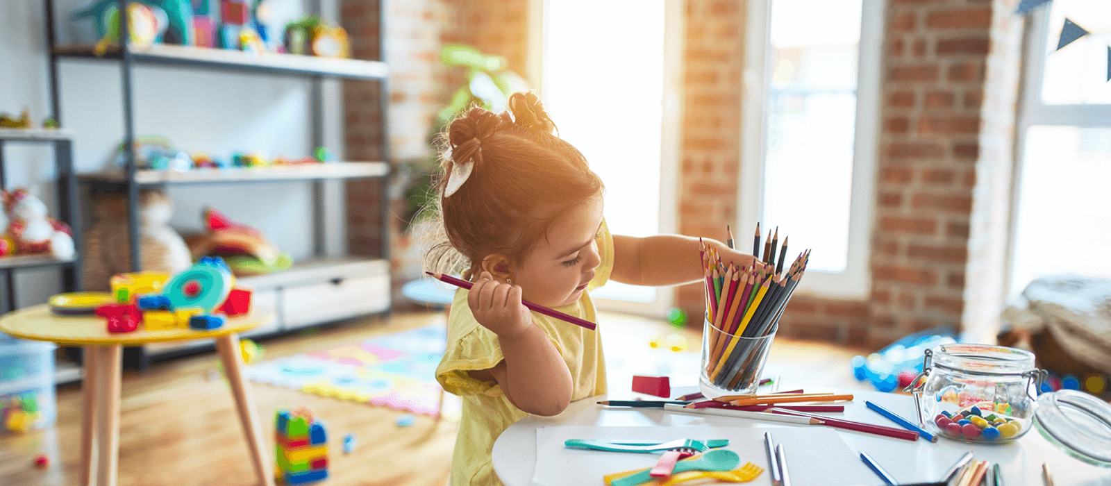 A small child selects a colored pencil while working on a colorful drawing.