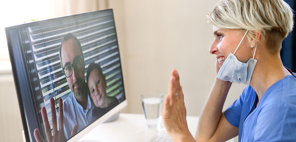A doctor smiles at a computer while talking to two patients during a telehealth appointment.